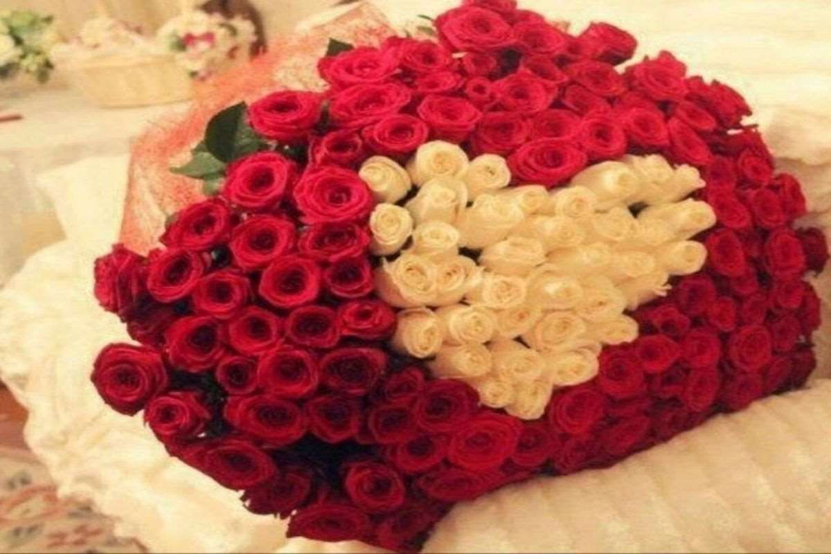 Bouquet of red and white roses, white roses in middle of bouquet make the shape of a heart
