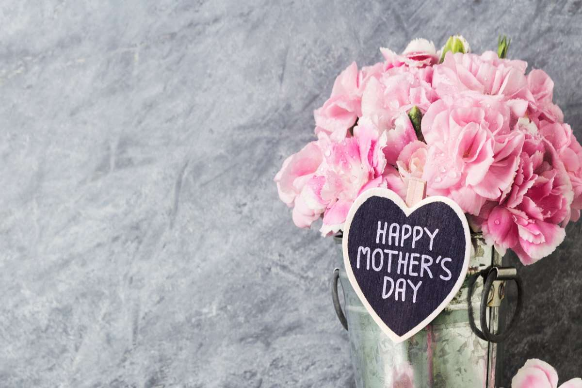 A bouquet of pink flowers in a medal circular bucket. Heart shaped sign on front of the bucket that says happy mother's day